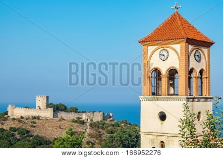 Bell Tower of the church of Agios Eleftherios in Neos Panteleimonas village and medieval fortress of Platamonas in the distance. Pieria Macedonia Greece