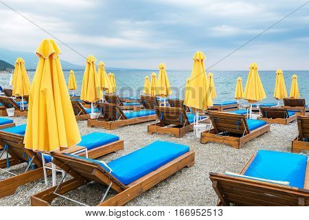 Beach umbrellas and empty lounge chairs on a cloudy day. Platamonas Pieria Macedonia Greece Europe