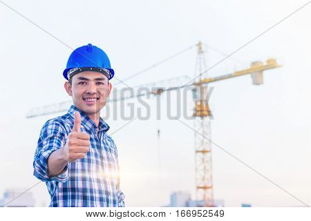 The engineer wear a blue safety helmet with construction site and crane background. He has smile because his project were success.