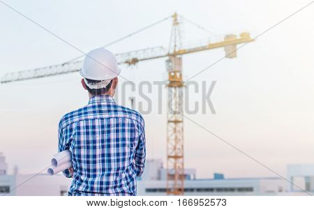 Portrait of architect wear white helmet safty hold the blueprint on construction site with crane background
