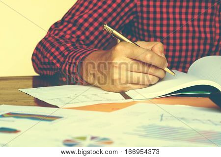 Business Man Writing Make Note About Expenses And Thinking With Problem At Home Office.