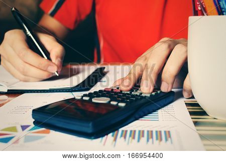 Close up of hand man calculate expenses and making note at home office.