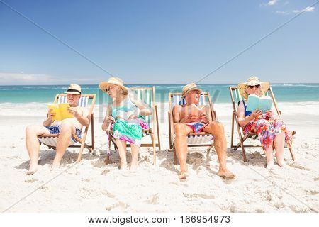 Senior friends reading books on beach chairs at the beach