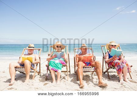 Senior friends reading books on beach chair at the beach