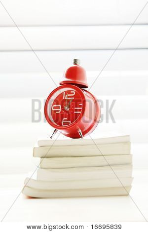 A red traditional alarm clock stand on books