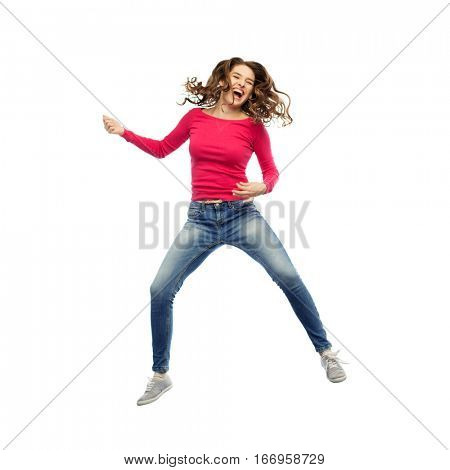 happiness, freedom, motion and people concept - smiling young woman jumping in air and pretending guitar playing over white background