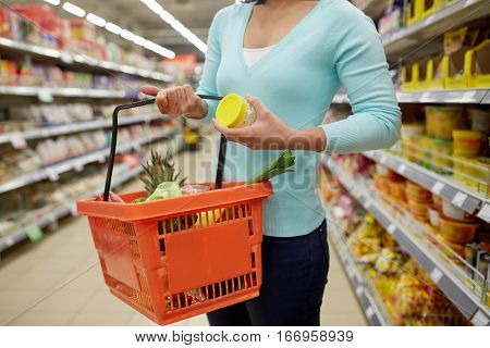 sale, shopping, consumerism and people concept - woman with food basket and jar at grocery store or supermarket