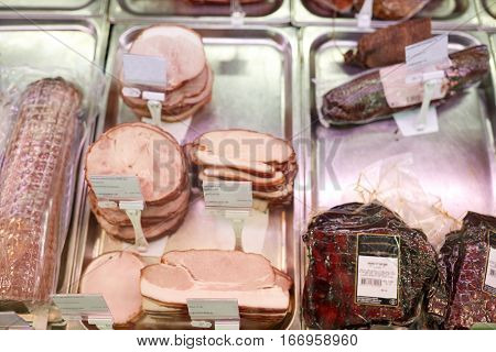 meat, sale and food concept - ham at grocery store stall