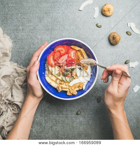 Yogurt, granola, seeds, fresh and dry fruits and honey in blue ceramic bowl in woman' s hands over grey background, top view, square crop, copy space. Clean eating, detox, dieting food concept