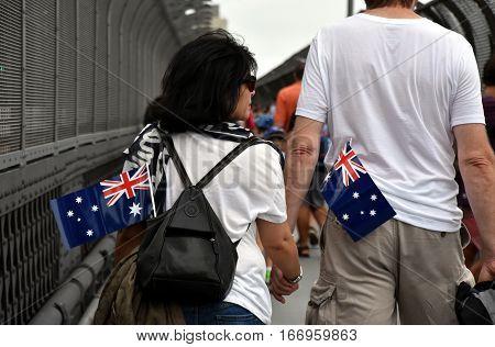 Sydney, Australia - January 26, 2016. A couple celebrating Australia Day in Sydney. Australia flags in the bag.