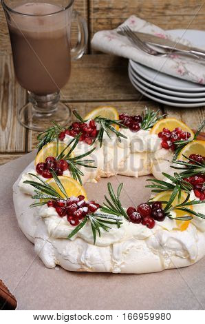 Pavlova cake in the form of a Christmas wreath of meringue with cream pomegranate cranberry rosemary sprigs