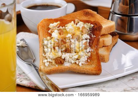 Crisp fresh toast ricotta honey and nuts for breakfast with orange juice and coffee