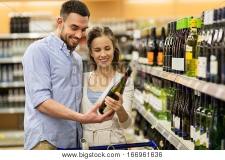 sale, consumerism, alcohol and people concept - happy couple with bottle of white wine and shopping cart at liquor store or supermarket
