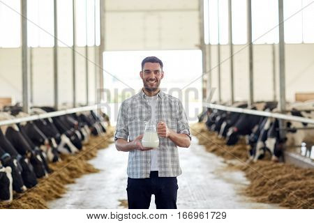 agriculture industry, farming, people and animal husbandry concept - happy young man or farmer with jug of cows milk in cowshed on dairy farm