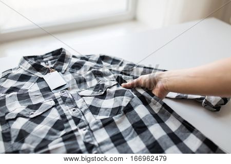 clothes, fashion, people and shopping concept - close up of hand holding checkered shirt with price tag