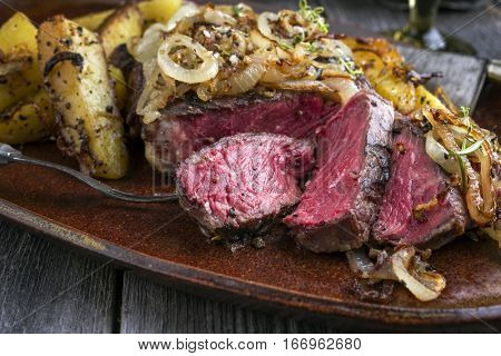 Wagyu Entrecote Steak Bleu with fried Onions and Potatoes