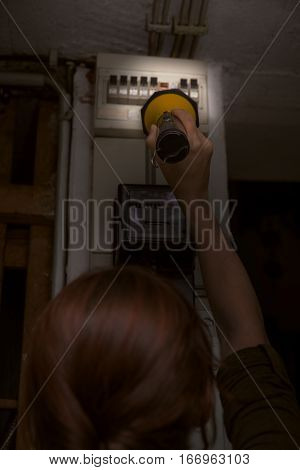 Blackout electricity cut woman with flashlight checking the breaker box fuse box