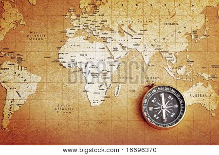An old brass compass on a Treasure map background