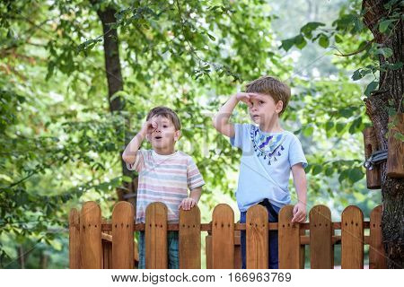 Two Little Brothers Playing Together Standing On Wooden Playground In The Summer Park. Kid Showing S
