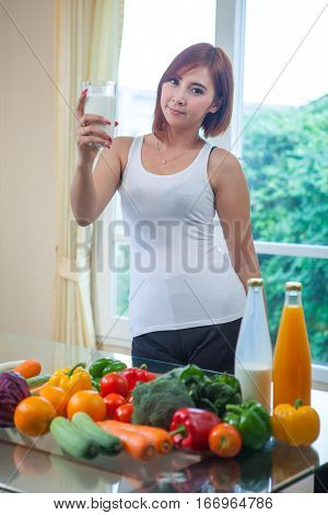 Young asian woman drinking milk in kitchen