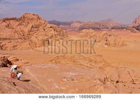 WADI RUM, JORDAN - NOVEMBER 13, 2010: A Jordanian man overlooking the Wadi Rum desert before climbing a mountain