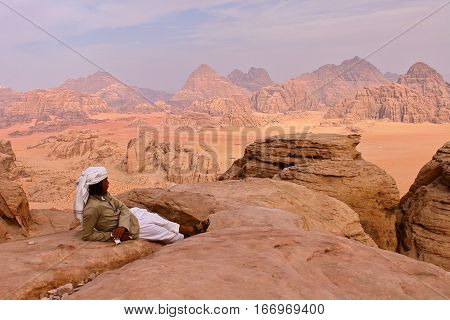 WADI RUM, JORDAN - NOVEMBER 12, 2010: A Jordanian man overlooking the Wadi Rum desert from the top of a mountain