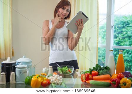 Young asian woman looking for a recipe on the internet in kitchen