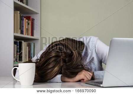 Tired girl resting her head on the table of working with computer. Female person upset or exhausted of studying or overworked too much time at laptop PC at home with bookshelf in background