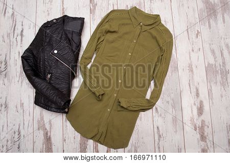 Fashion concept. Black leather jacket and khaki color blouse. Top view space for text