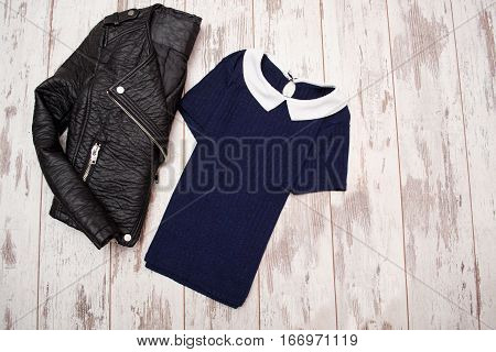 Fashion concept. Black leather jacket and a blue shirt with a white collar. Top view space for text