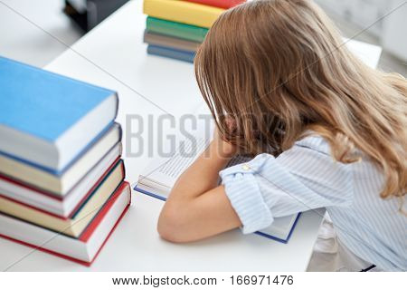 education, learning, children and people concept - close up of student girl with many books at school desk