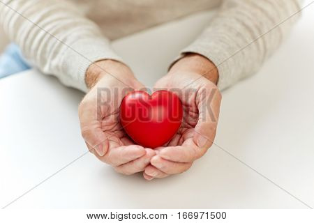 valentines day, love, charity, donation and people concept - close up of senior man with red heart in hands