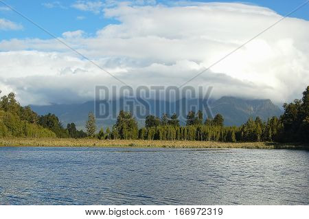Clouds behind Lake Matheson in the Glaciers Country of the South Island of New Zealand