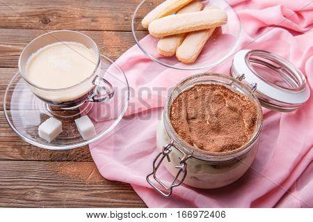 Tiramisu, coffee , savoiardi on pink cloth on brown wooden table