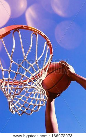 Low angle view of determined young man dunking basketball into hoop against clear blue sky