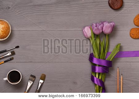 Lilac tulips and coffee with biscuits in the lilac wooden table of the artist. Banner template layout mockup for Woman Day, Valentines Day and Teacher's Day. Photo for posts, blogs, advertising and news.