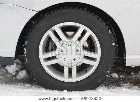 Closeup of a new winter tire in a cold snowy day