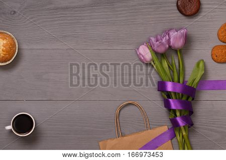 Lilac tulips and coffee with biscuits in the lilac wooden table. Banner template layout mockup for Woman Day, Valentines Day and Teacher's Day. Photo for posts, blogs, advertising and news.