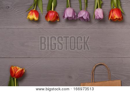 Lilac and red tulips and gift bag in the lilac wooden table. Banner template layout mockup for Woman Day, Valentines Day and Teacher's Day. Photo for posts, blogs, advertising and news.
