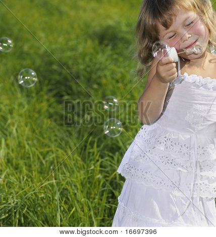 little girl blowing bubbles on green grass