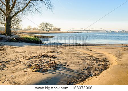 Small sandy beach along a wide Dutch river. It is in the late afternoon of a sunny day in the winter season. In the background a large arch bridge is visible.