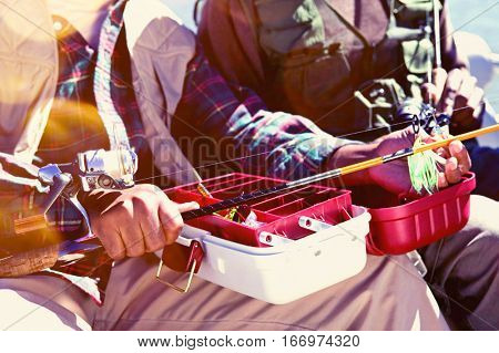 Man Using Tackle Box and Preparing Fishing Pole