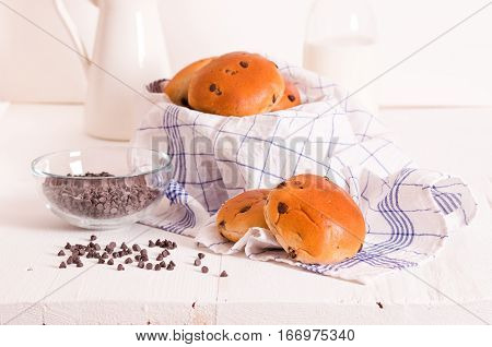 Chocolate chip brioche with milk bottle on wooden table.