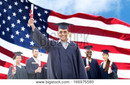 education, graduation and people concept - group of happy international students in mortarboards and bachelor gowns with diplomas over american flag background