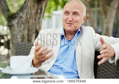 Portrait of agitated mature man gesturing actively white having conversation with someone out of frame at outdoor cafe lounge on bright summer day