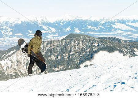Young Snowboarder Holding His Board In Hand And Climbing To The Top Of A Mountain