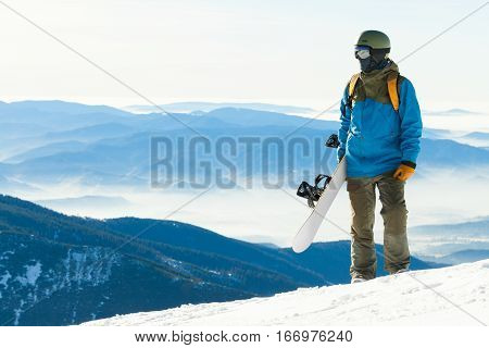 Young Snowboarder Looking At A Landscape From The Top Of A Mountain