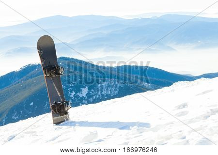 Snowboard Thrusted Into Snow At The Very Top Of A Mountain