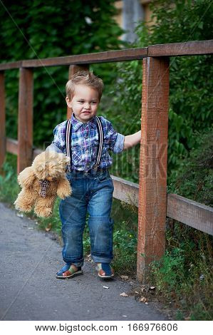 Cute little boy standing near a brown wooden , stylish jeans with suspenders and plaid shirt. Memories of childhood and carefree