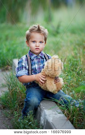 Little cute boy sitting and hugging his Teddy bear, stylish jeans with suspenders and plaid shirt. Memories of childhood and carefree